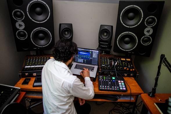 hombre creando música con laptop  Ford.